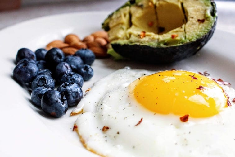 an egg, nuts, avocado and blueberries