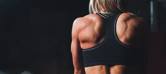 a woman's back in a tank top revealing muscles